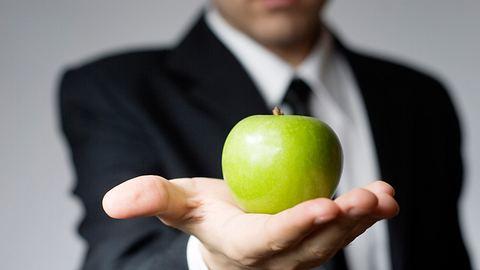 Ein Mann hält einen grünen Apfel in die Kamera - Foto: iStock / dgt79