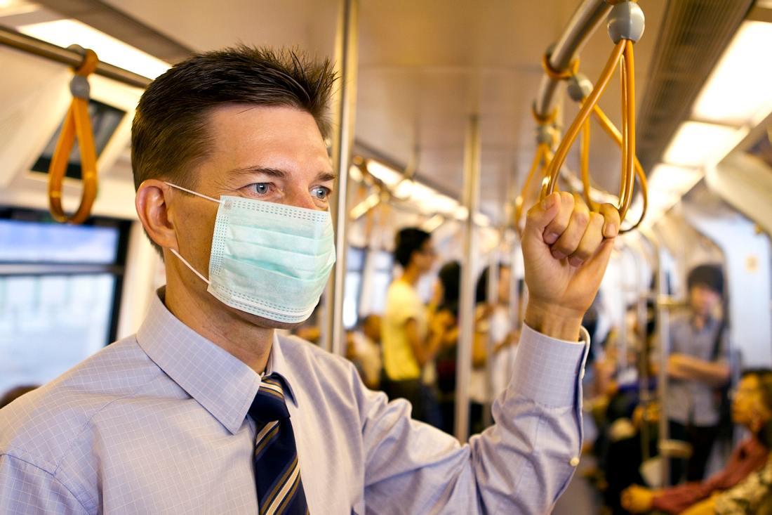 Mann mit Mundschutz in der U-Bahn