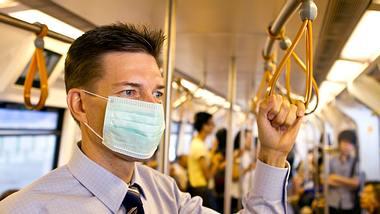Mann mit Mundschutz in der U-Bahn - Foto: iStock / joakimbkk