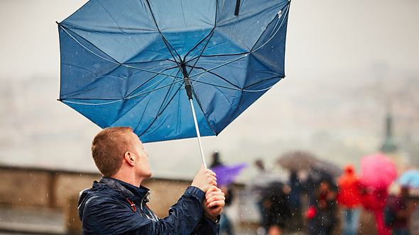 Mann mit umgeklapptem Regenschirm - Foto: iStock / Chalabala