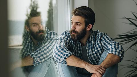 Mann sitzt nachdenklich am Fenster - Foto: iStock / skynesher