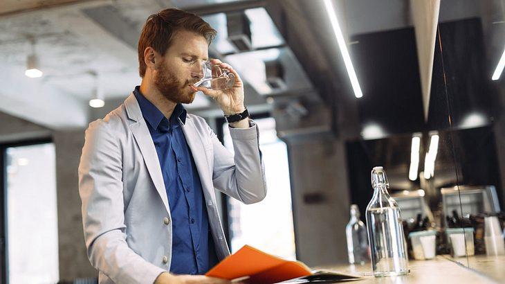 Mann trinkt lässig eine Glas Wasser