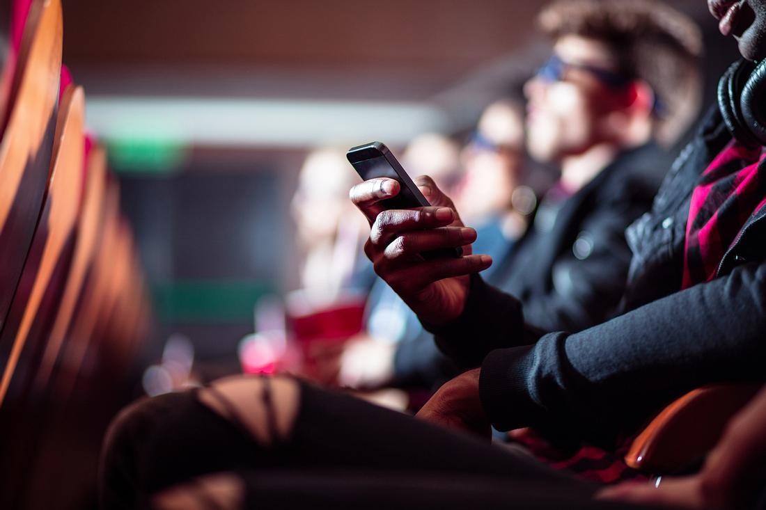 Frau mit Handy im Kino
