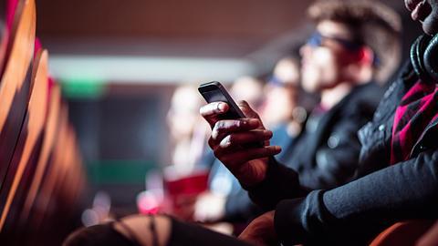 Frau mit Handy im Kino - Foto: iStock/izusek