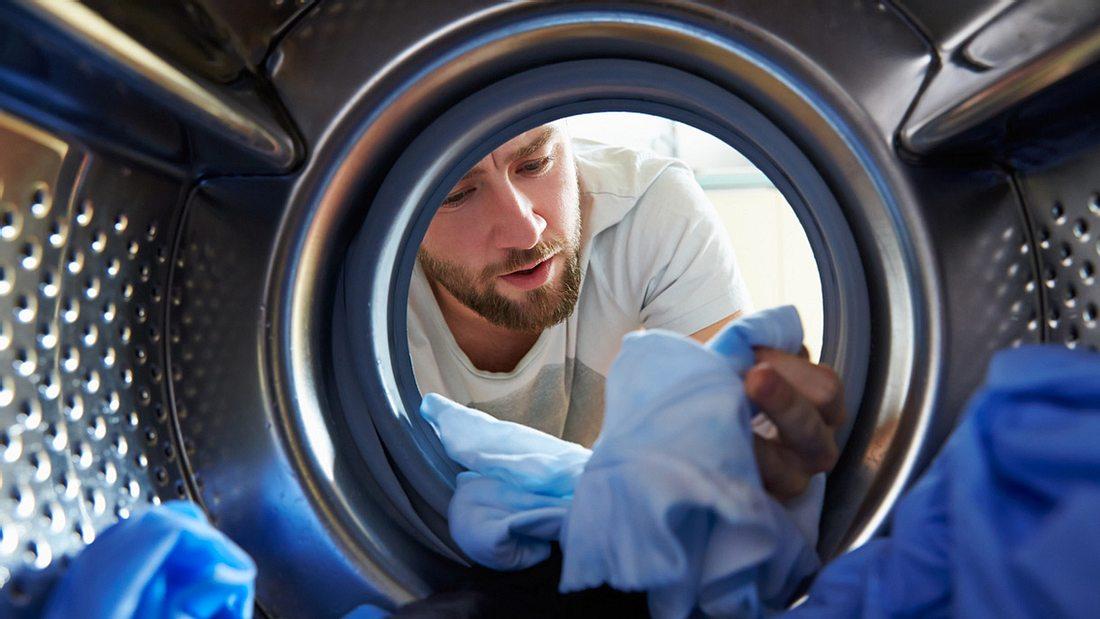 Mann wäscht seine dreckige Wäsche