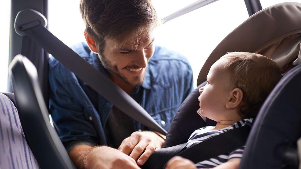 Junger Mann arretiert sein Kind im Kindersitz - Foto: iStock / PeopleImages