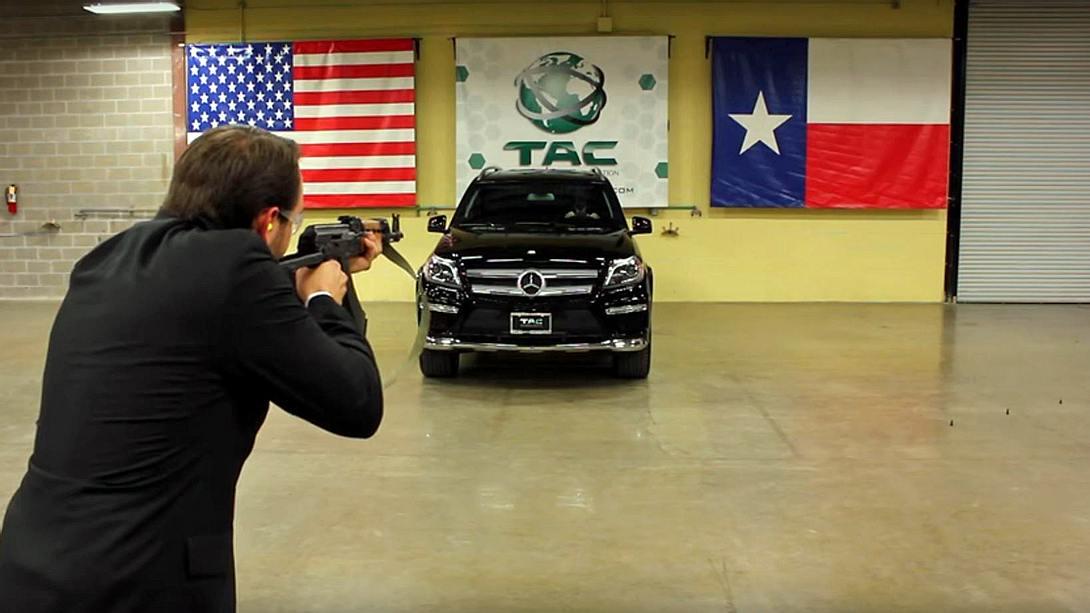 Mann sitzt in Mercedes, der mit einer AK-47 beschossen wird