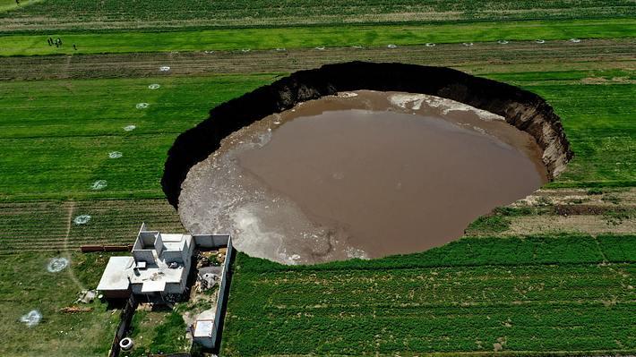 Krater von Zacatepec, angrenzendes Haus, Luftaufnahme - Foto: Getty Images / JOSE CASTANARES