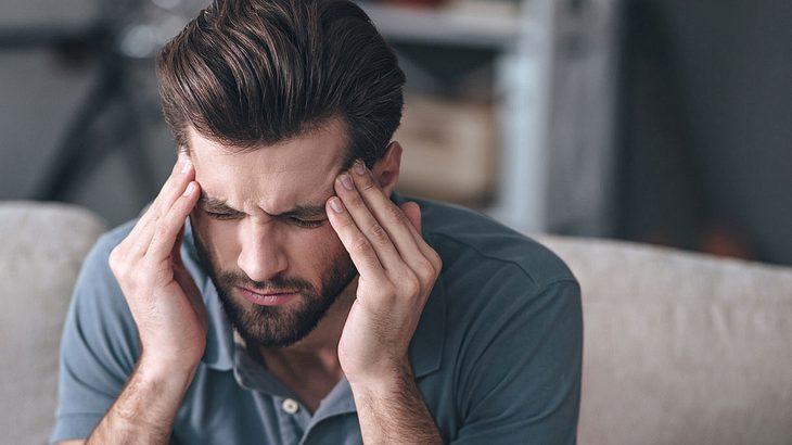 Mann mit Kopfschmerzen / Migräne