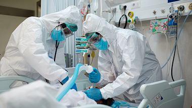 Zwei Krankenhausmitarbeiter kümmern sich um einen Patienten - Foto: iStock/Tempura
