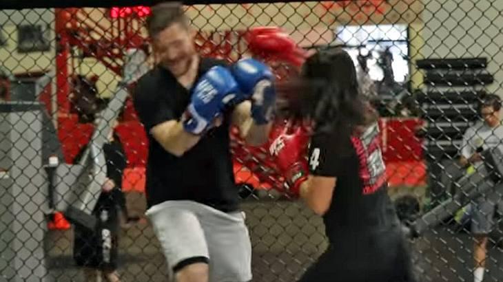 Ein in MMA trainiertes Mädchen kämpft gegen einen erwachsenen Mann