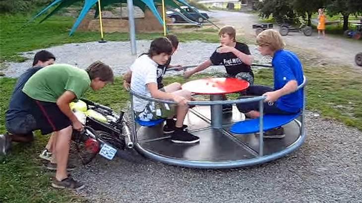 Jugendliche halten ein Moped-Rad an an Spielplatz-Karussell