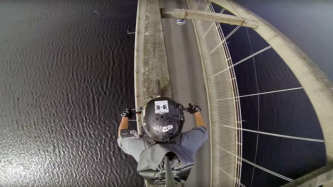 Ein Motocross-Fahrer des Stunt Freaks Team überquert eine Brücke auf dem Brückenbogen