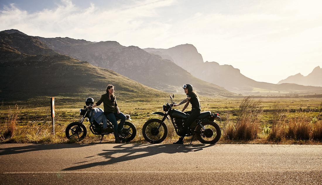 Zwei Motorradfahrer stehen auf der Straße, im Hintergrund sind Berge zu sehen
