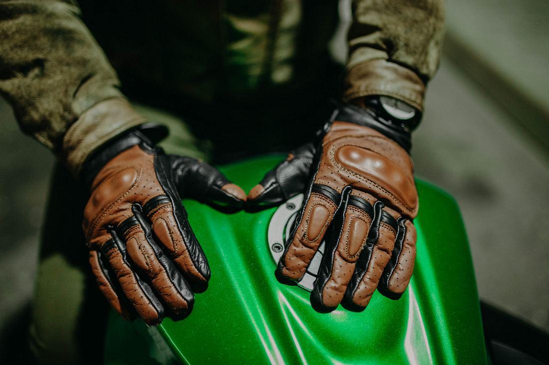 Motorradfahrer trägt braune Lederhandschuhe
