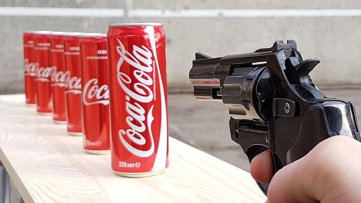 Mr. Gear schießt mit einem Revolver auf Cola-Dosen