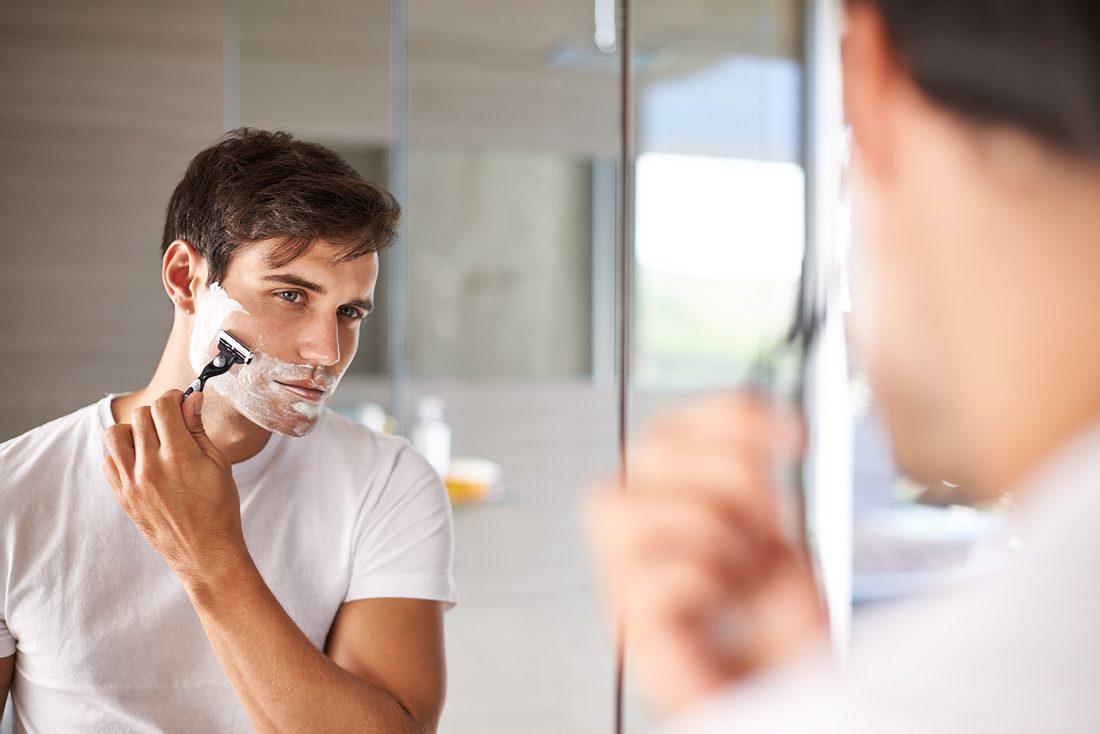 Mann benutzt einen Nassrasierer