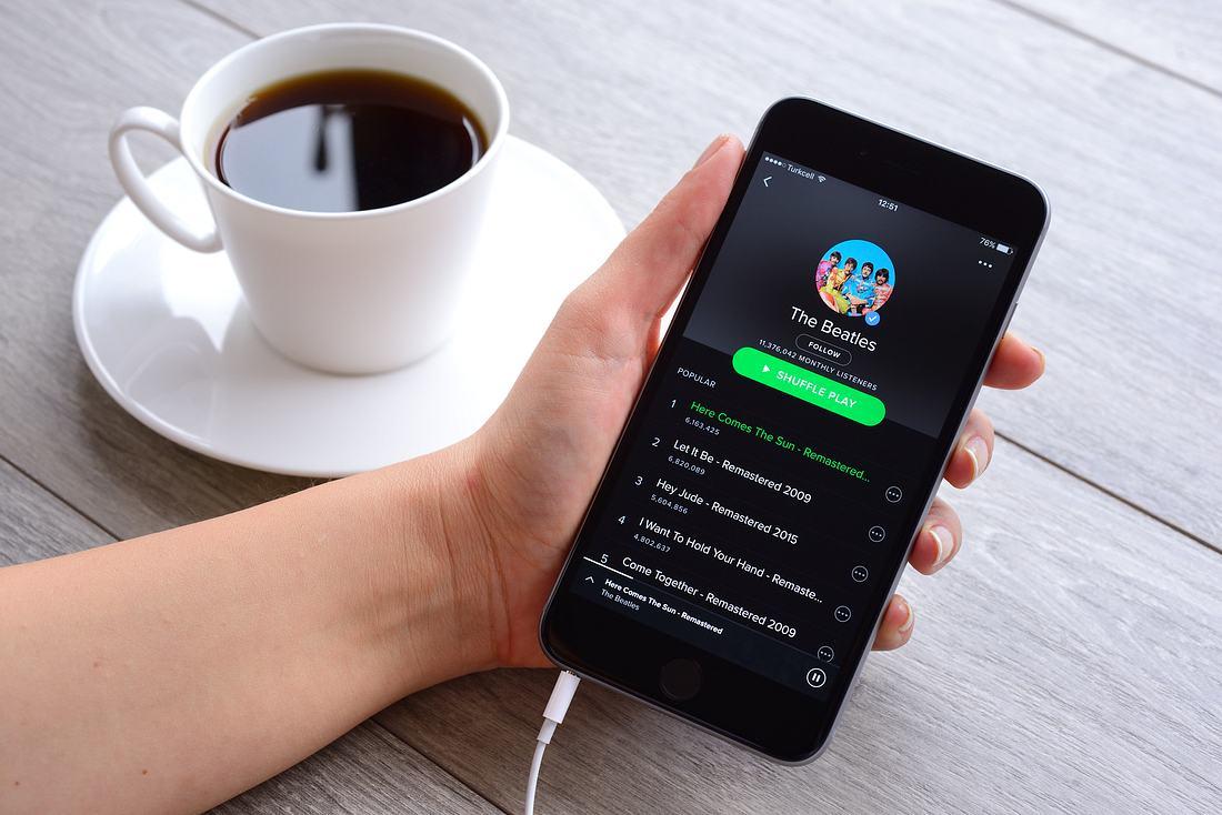Hand hält Smartphone, auf dem die Spotify-App läuft