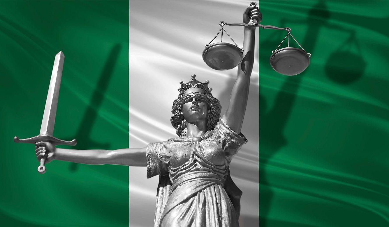 Statue des Gottes der Gerechtigkeit Themis vor der Flagge Nigerias