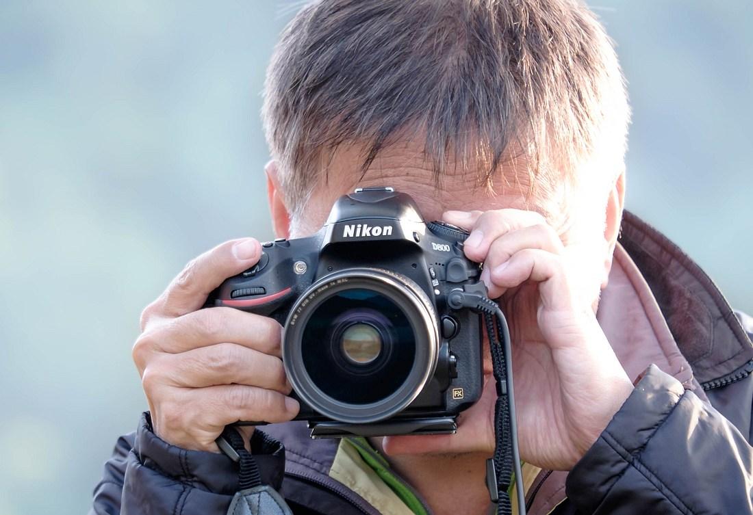 Mann mit Nikon-Fotokamera