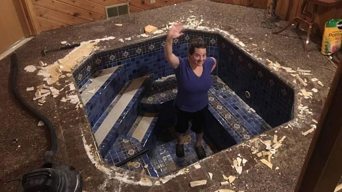 Frau steht in einem römischen Bad und winkt