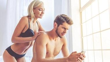 Junges, halbnacktes Paar auf Bett, beide schauen auf ein Handy - Foto: IMAGO / agefotostock