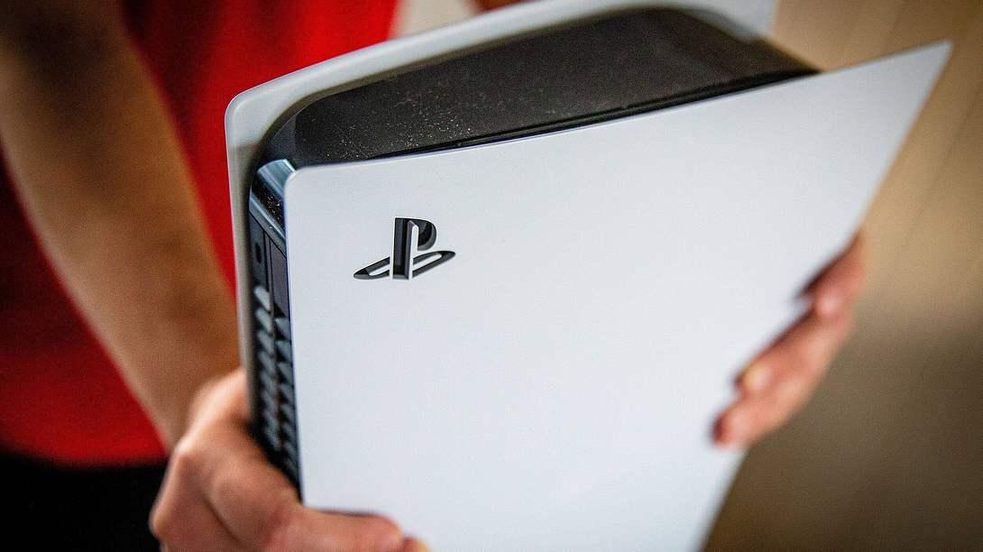Mann hält ausgepackte PlayStation 5 in den Händen - Foto: IMAGO / ANP