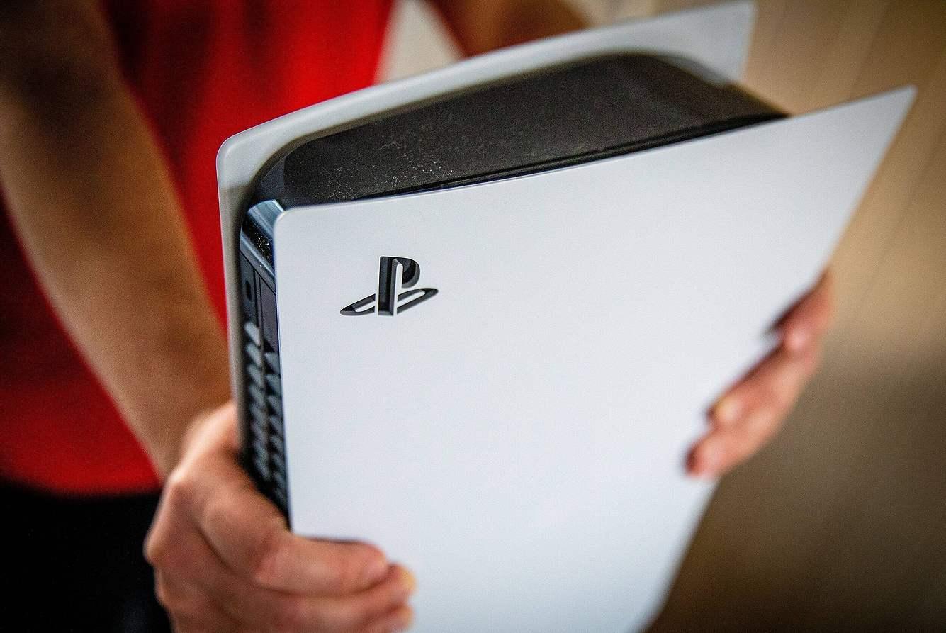 Mann hält ausgepackte PlayStation 5 in den Händen