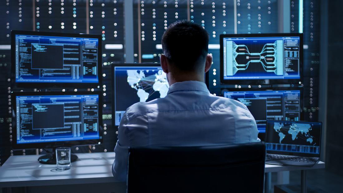 Mann sitzt vor fünf Monitoren