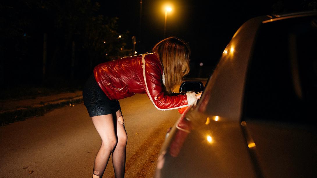 Prostituierte lehnt sich an Autofenster - Foto: iStock / microgen