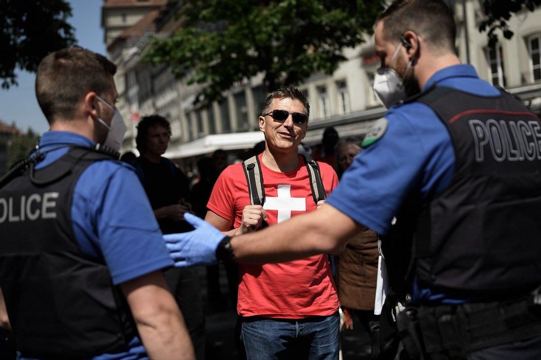 Mann mit Schweiz-Shirt vor Polizisten