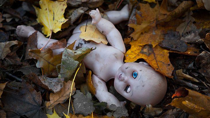 Creepy Puppe auf dem Waldboden