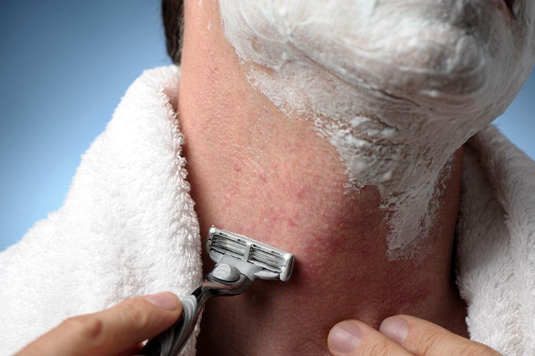 Mann rasiert sich mit einem Nassrasierer