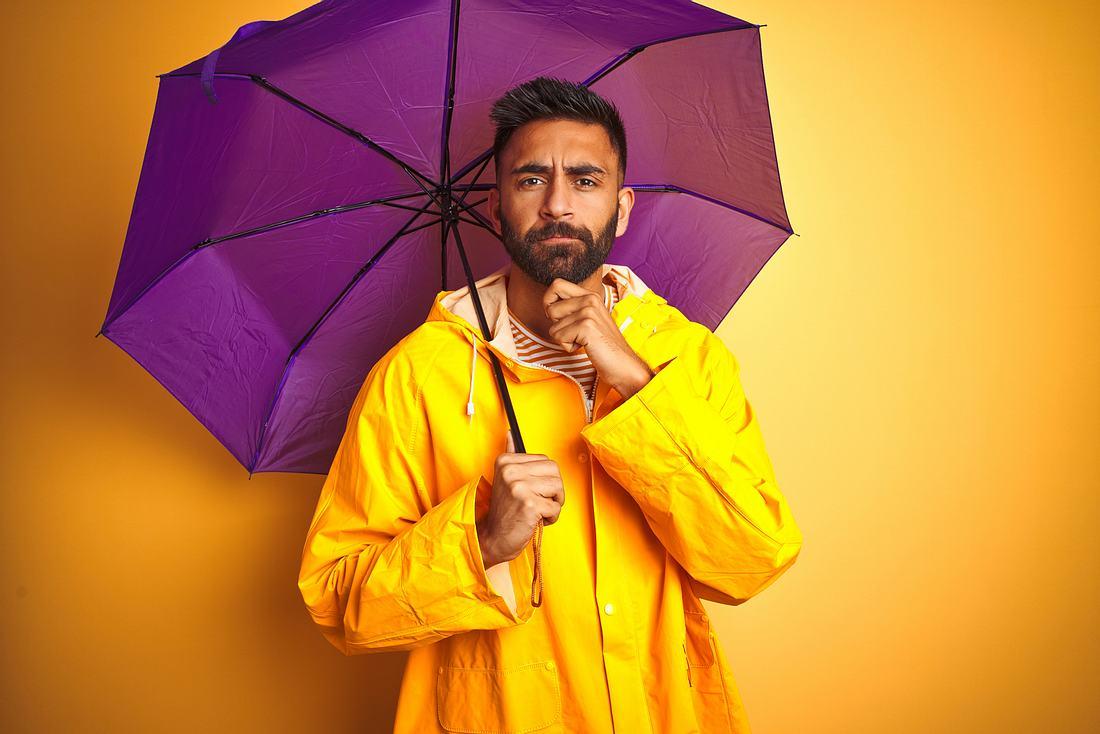 Herr mit Regenjacke und Regenschirm