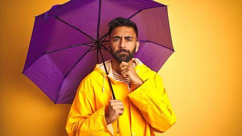 Herr mit Regenjacke und Regenschirm - Foto: iStock/AaronAmat