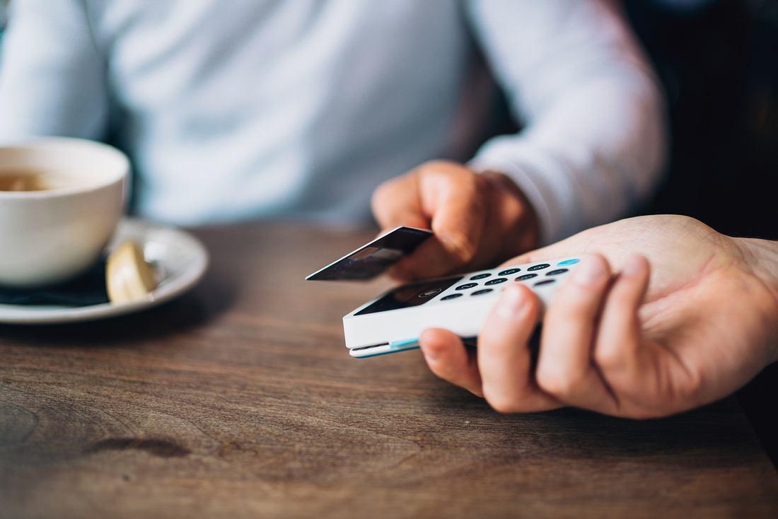 Mann bezahlt kontaktlos mit seiner Kreditkarte