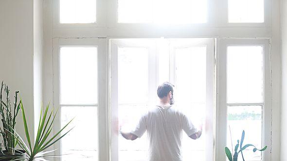 Mann öffnet seine Fenster - Foto: iStock / aydinynr