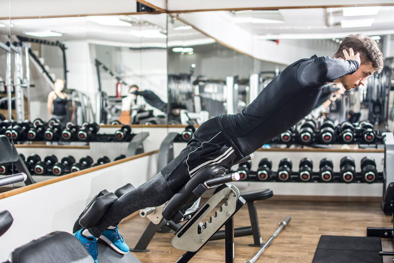 Ein Mann trainiert auf einem Rückentrainer im Fitnessstudio