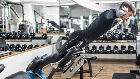 Ein Mann trainiert auf einem Rückentrainer im Fitnessstudio - Foto: iStock/Bojan89