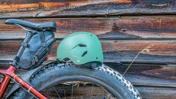 Ein Fahrrad mit Satteltasche steht an eine Holzwand gelehnt - Foto: iStock/marekuliasz