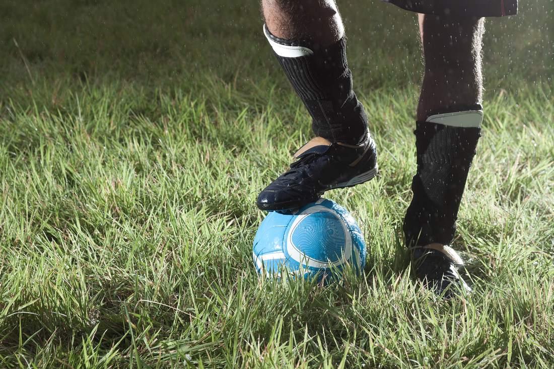 Ein Mann mit einem Fußball und Schienbeinschonern auf dem Rasen