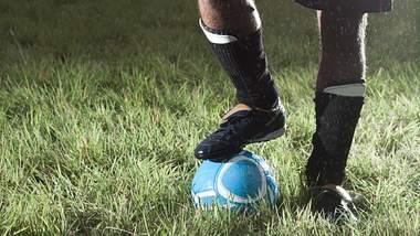 Ein Mann mit einem Fußball und Schienbeinschonern auf dem Rasen - Foto: iStock/edenexposed