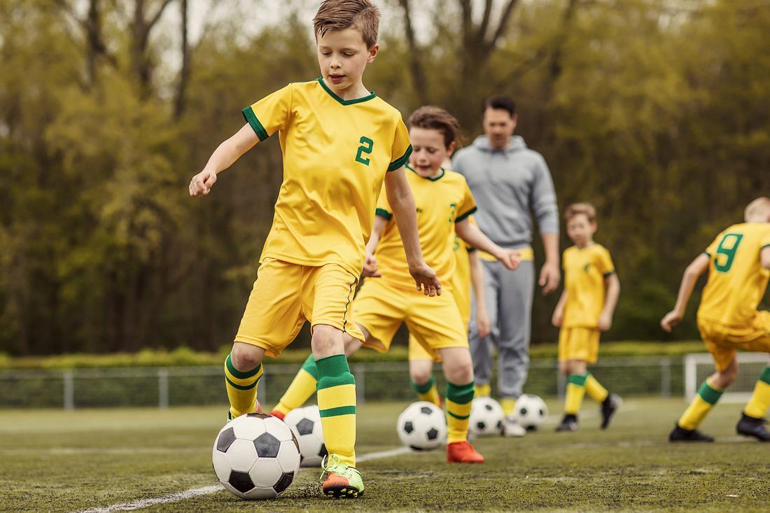 Ein Kind spielt Fußball und hat dabei Schienbeinschoner für Kinder an