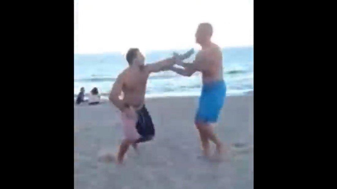 Schlägerei zwischen Betrunkenem und einem Vater am Strand.