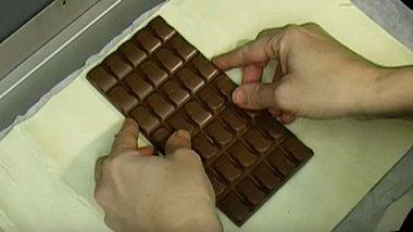 Er legt eine Tafel Schokolade in den Ofen