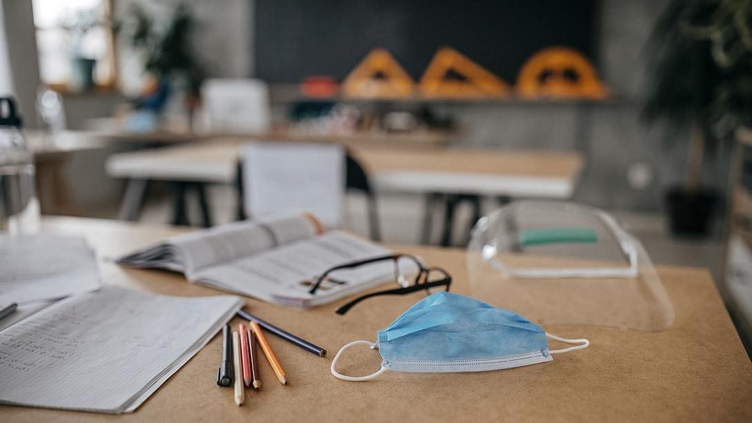 Maske auf einer Schulbank in leerer Klasse - Foto: iStock / mixetto