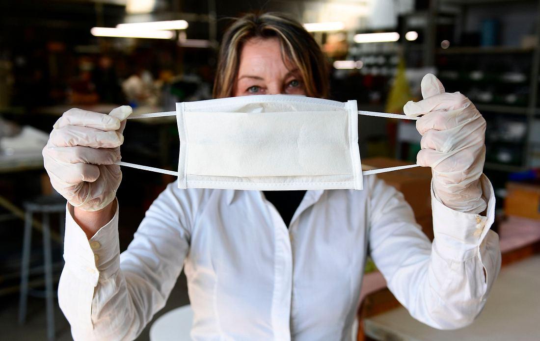 Frau hält Schutzmaske hoch