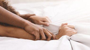 Hände, die sich am Bettlaken festhalten - Foto: iStock / Prostock-Studio