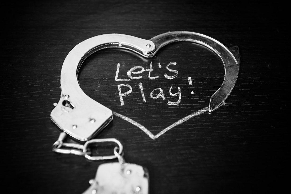 Geöffnete Handschellen liegen auf einem Holztisch zu einem Herz geformt