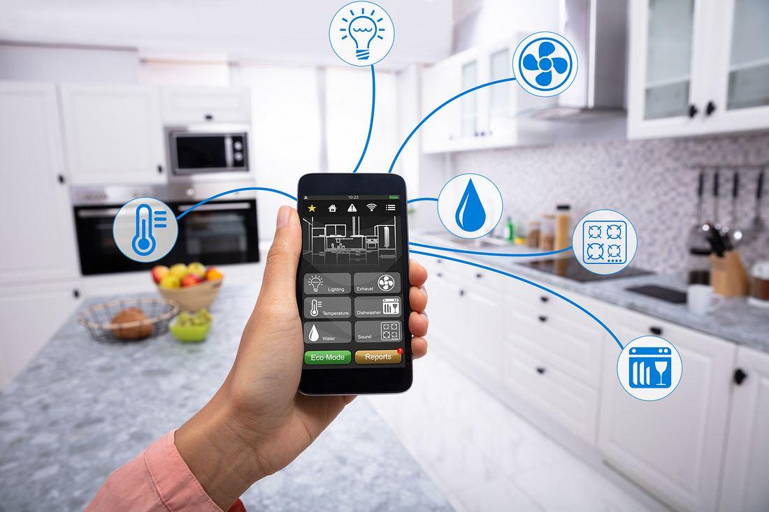Ein Mann hält ein Handy in der Hand über das er seine Smart Home Steckdose kontrolliert